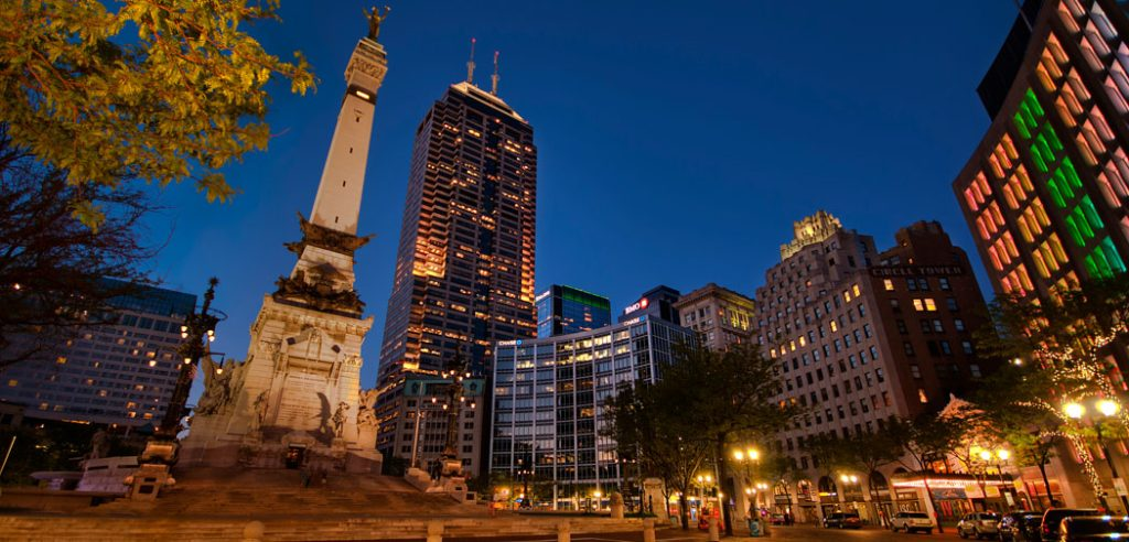 The Soldiers and Sailors Monument reaches into a blue, night sky crowded with tall buildings in Indianapolis.