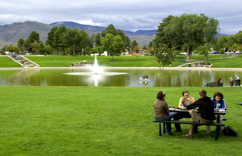 A group of people city at a picnic table in front of a pond in a park that is beyond high mountains in Los Alamos.