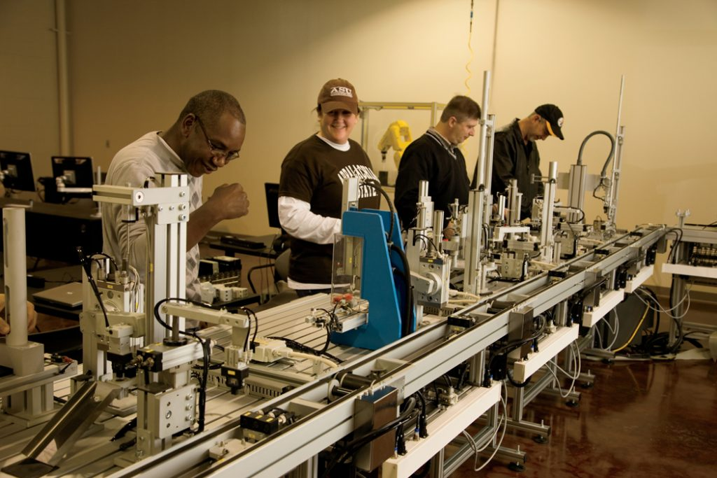 Students work with robots on a small scale production line at Wilkes Community College in Wilkesboro, NC.