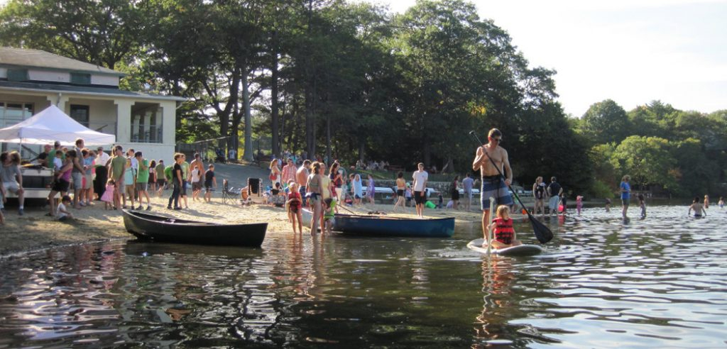 People play on the beach at Crystal Lake in Newton, MA