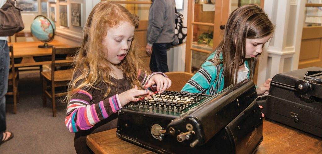 Girls play on a typewriter at the Oak Ridge Childrens Museum