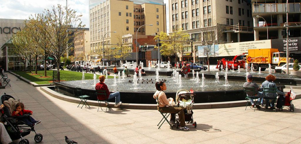 People with children gather around a fountain in White Plains, NY.