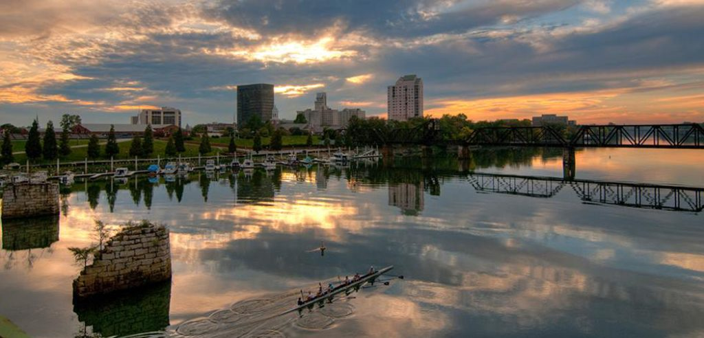 A crew team paddles across the river as the sun rises over the city of Augusta, GA.