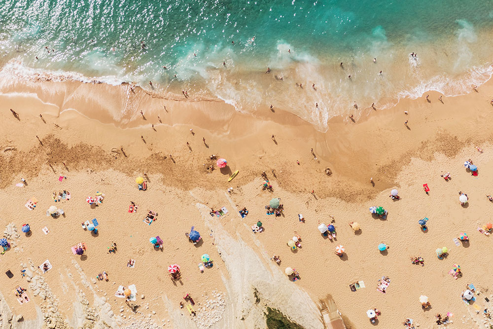 Stock photo of beach lined with umbrellas and people during summer